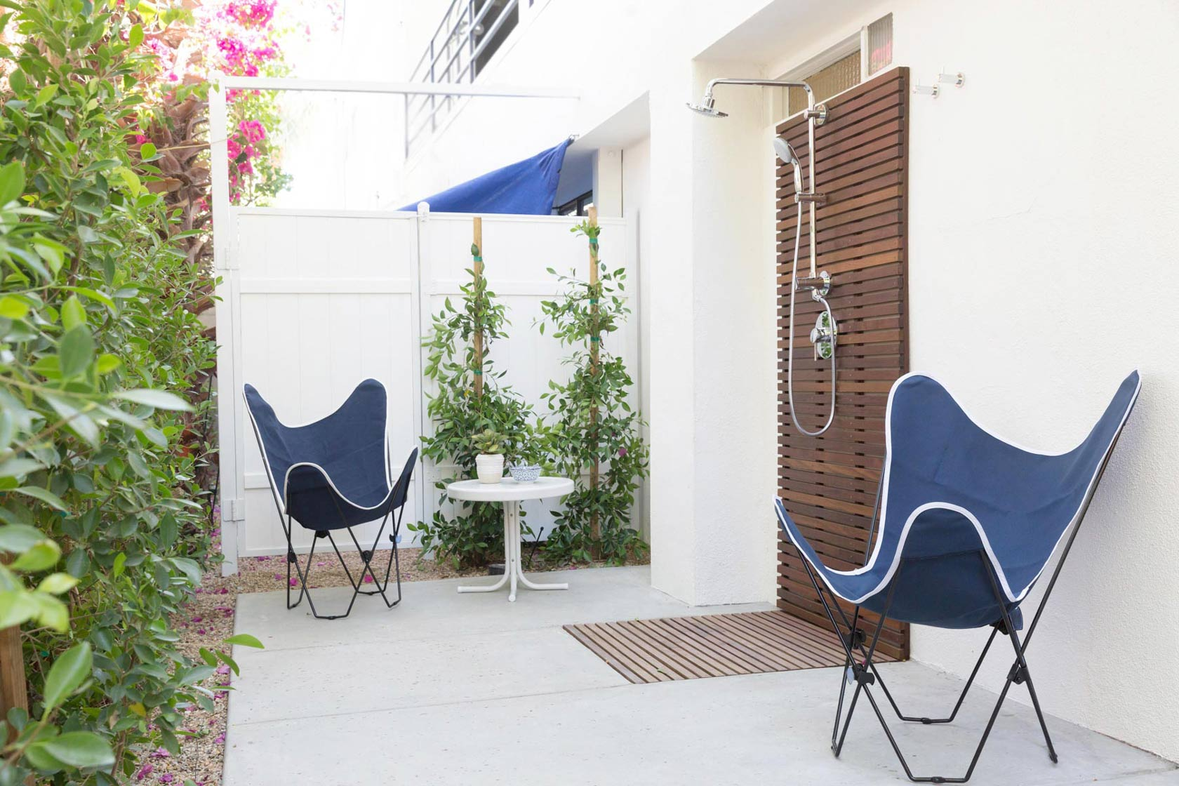 guest room patio area with outdoor shower and butterfly chairs